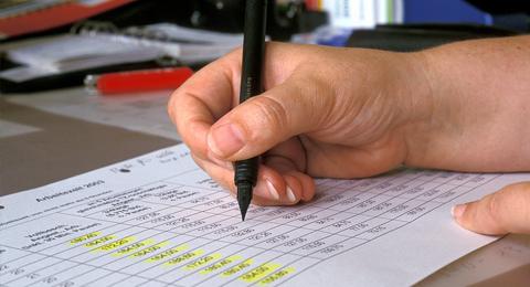 Das Bild zeigt die Hand eines Studierenden, der ein Formular ausfüllt. Foto & Copyright: Jürgen Haacks / Uni Kiel