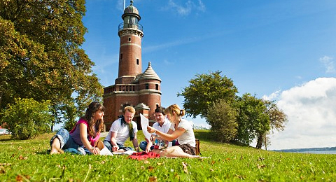 The picture shows students having a meal during a short break in front of a lighthouse. Copyright: Uni Kiel